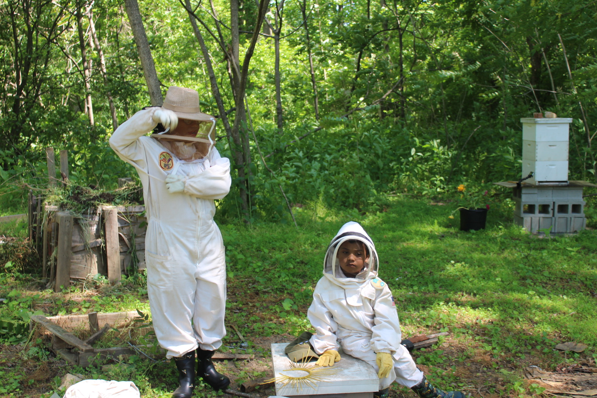 Samantha and her son in beekeeping suits in a backyard.