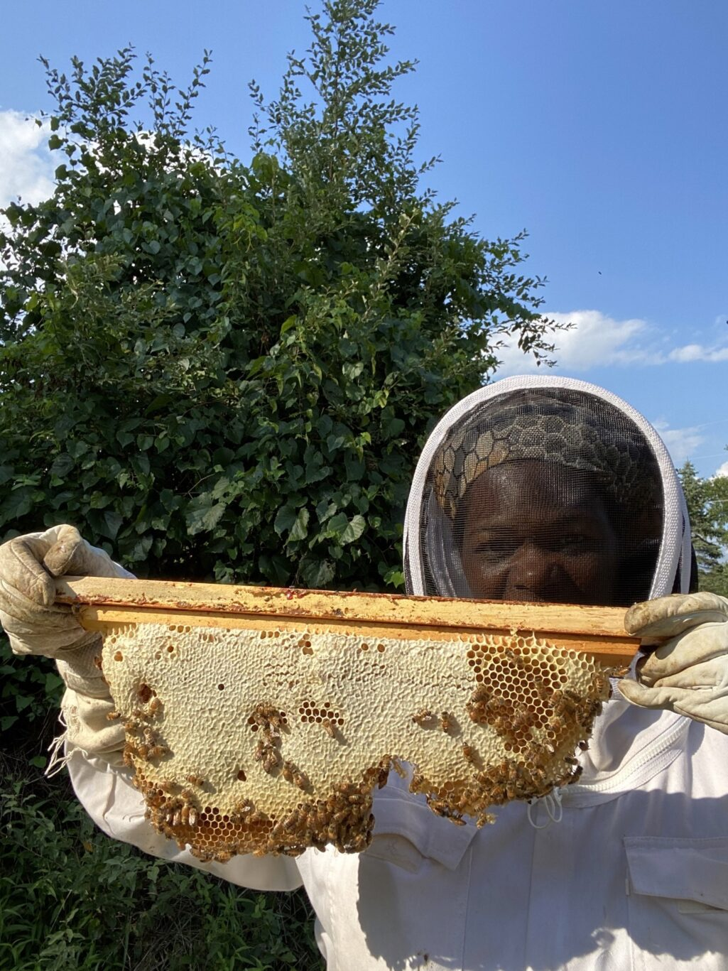 Tameeka holding a frame of bees and honey.